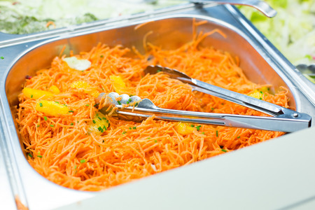 spicy cooking: food, catering, eating and cooking concept - close up of spicy korean carrot salad with tongs in metallic container Stock Photo