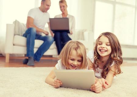 niños jugando videojuegos: familia, los niños, la tecnología y el concepto de casa - hermana sonriente con la tableta informática PC y los padres en la parte posterior con el ordenador portátil