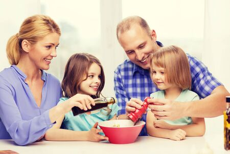 hapiness: food, family, children, hapiness and people concept - happy family with two kids making dinner at home Stock Photo