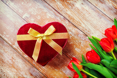 chocolate candy: flowers, valentines day and holidays concept - close up of red tulips and heart shaped chocolate box on wooden table Stock Photo