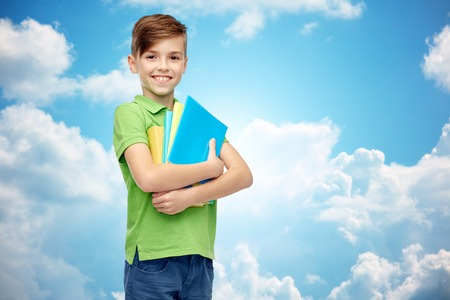 pre adolescent boy: childhood, school, education and people concept - happy smiling student boy with folders and notebooks over blue sky and clouds background Stock Photo