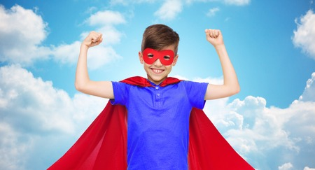 pre adolescent boys: carnival, childhood, power, gesture and people concept - happy boy in red super hero cape and mask showing fists over blue sky and clouds background