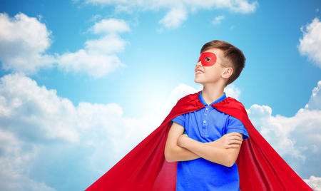 pre teen boys: carnival, childhood, power, gesture and people concept - happy boy in red super hero cape and mask over blue sky and clouds background