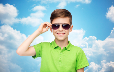 pre teen boys: childhood, fashion, accessory, style and people concept - happy smiling boy in sunglasses and green polo t-shirt over blue sky and clouds background
