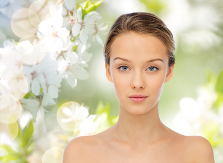 natural face: beauty, people, organic, eco and health concept - young woman face and shoulders over green natural background with cherry blossoms