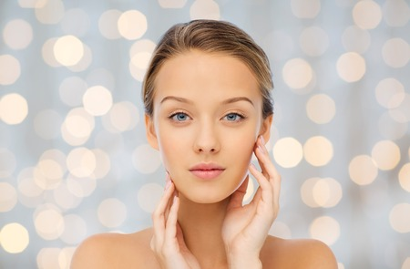 beauty and health: beauty, people and health concept - young woman with bare shoulders touching her face over holidays lights background