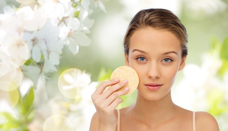 removing make up: beauty, people, toiletry and skincare concept - young woman cleaning face with exfoliating sponge over cherry blossom background
