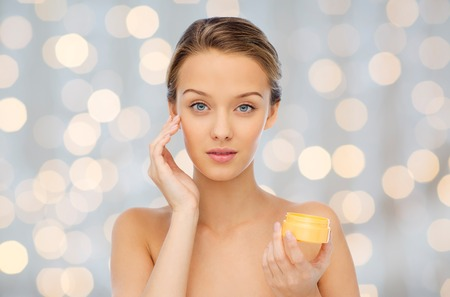 applying: beauty, people, cosmetics, skincare and cosmetics concept - young woman applying cream to her face over holidays lights background