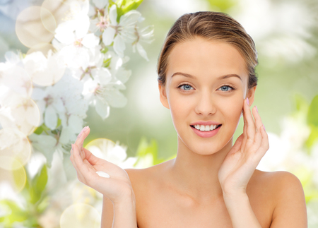 fresh cream: beauty, people, cosmetics, skincare and health concept - happy smiling young woman applying cream to her face over green natural background with cherry blossoms