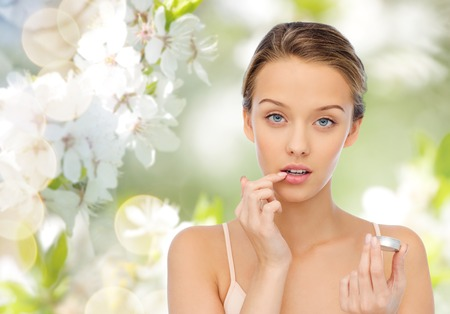 girl holding flower: beauty, people and lip care concept - young woman applying lip balm to her lips over green natural background with cherry blossoms Stock Photo