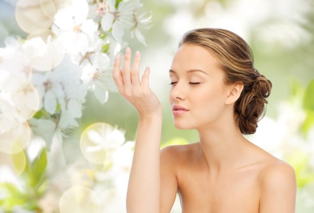 fragrance: beauty, aroma, people and body care concept - young woman smelling perfume from wrist of her hand over green natural background with cherry blossoms