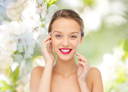 make up: beauty, people and health concept - smiling young woman face with pink lipstick on lips and shoulders over green natural background with cherry blossoms Stock Photo