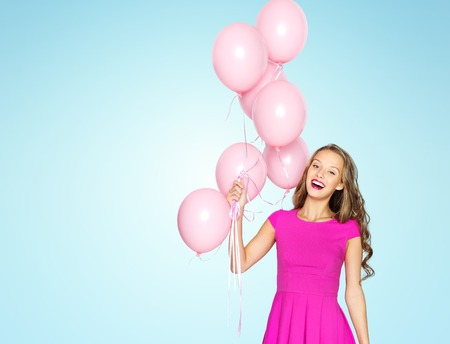 fashion and beauty: beauty, people, style, holidays and fashion concept - happy young woman or teen girl in pink dress with helium air balloons over sky blue background Stock Photo