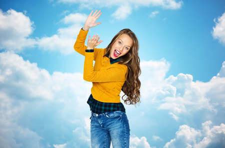 aplaudiendo: people, style and fashion concept - happy young woman or teen girl in casual clothes having fun and applauding over blue sky and clouds background