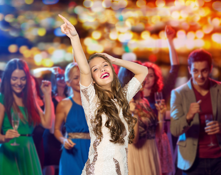 people, holidays and nightlife concept - happy young woman or teen girl in fancy dress with sequins and long wavy hair dancing at night club party over crowd and lights background Stockfoto