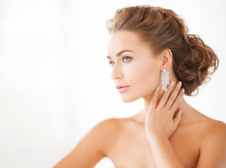 jewel: beauty and jewelery concept - woman wearing shiny diamond earrings Stock Photo
