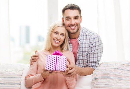 romantic man: relationships, love, people, birthday and holidays concept - happy man giving woman gift box at home