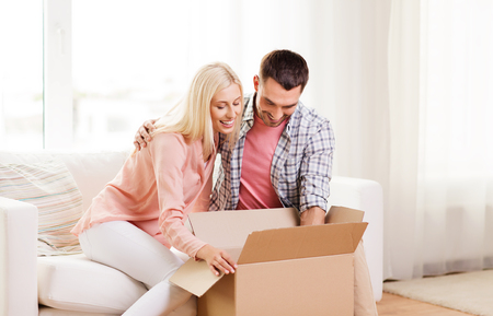 postal: people, delivery, shipping and postal service concept - happy couple opening cardboard box or parcel at home