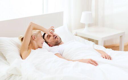 nariz: las personas, la familia, la hora de acostarse y el concepto de pareja - mujer feliz cierre de la nariz a su hombre que ronca duerme en cama en su casa Foto de archivo