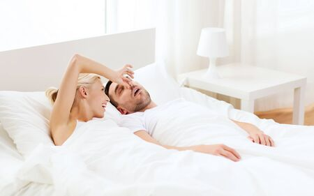 snoring: people, family, bedtime and couple concept - happy woman closing nose to her snoring man sleeping in bed at home Stock Photo