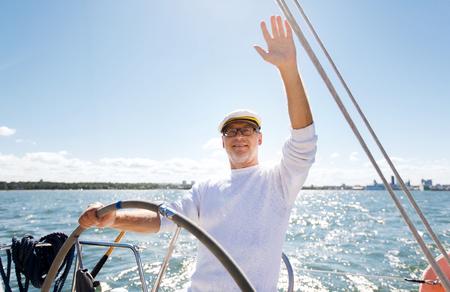 timon de barco: la vela, la edad, el turismo, los viajes y el concepto de la gente - hombre mayor feliz en el sombrero de capitán en el volante y agitando la mano barco de vela o yate que flota en el mar