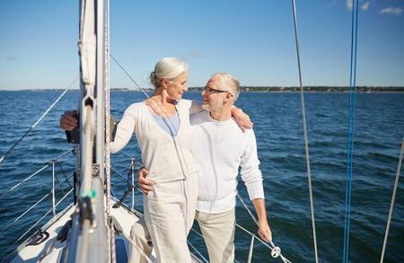 항해, 나이, 관광, 여행 및 사람들이 개념 - 행복 한 고위 커플 항해 보트 또는 바다에 떠있는 요트 갑판에 껴 안고