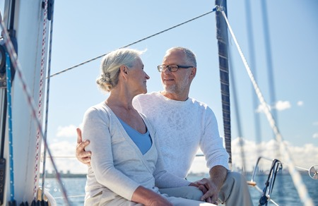sailing, age, tourism, travel and people concept - happy senior couple hugging and talking on sail boat or yacht deck floating in sea