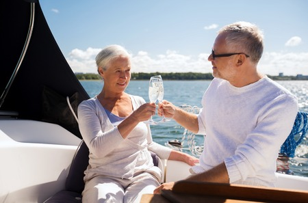 sailing, age, travel, holidays and people concept - happy senior couple clinking champagne glasses on sail boat or yacht deck floating in sea Foto de archivo