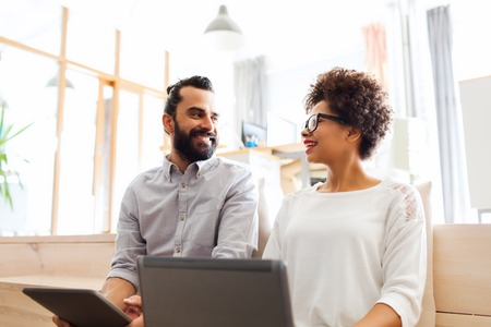 mujer trabajadora: negocio, puesta en marcha, la tecnolog�a y el concepto de la gente - feliz equipo creativo internacional con el ordenador port�til y la tableta de ordenador PC en la oficina Foto de archivo