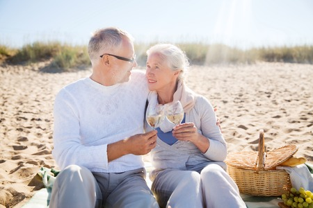 anniversary beach: family, age, travel, tourism and people concept - happy senior couple having picnic and talking on summer beach Stock Photo
