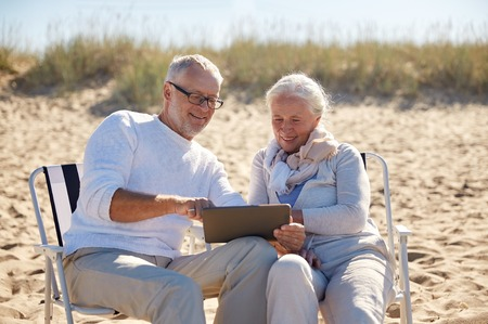 people relaxing: family, age, travel, tourism and people concept - happy senior couple with tablet pc computer resting in folding chairs on summer beach Stock Photo