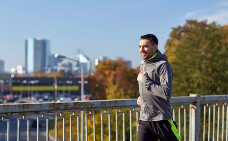 people   lifestyle: fitness, sport, people and lifestyle concept - happy young man running over city bridge