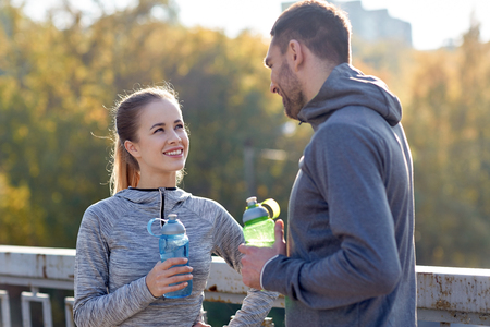 young couple: fitness, sport, people and lifestyle concept - smiling couple with bottles of water outdoors Stock Photo