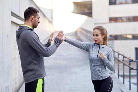 fitness, sport, vechtsporten, zelfverdediging en mensen concept - tevreden vrouw met personal trainer die staking buiten
