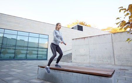 step by step: fitness, sport, people and healthy lifestyle concept - woman exercising on bench outdoors