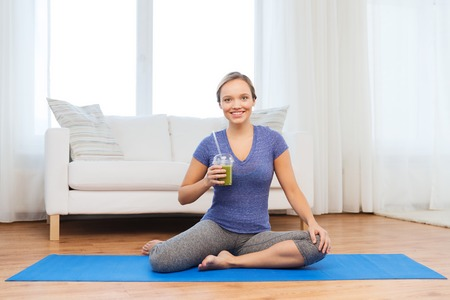 WOMAN FITNESS: fitness, sport, people, diet and healthy lifestyle concept - happy woman with cup of smoothie sitting on mat at home Stock Photo