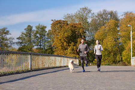 hispanic people: fitness, sport, people and lifestyle concept - happy couple with dog running outdoors