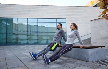 outdoor bench: fitness, sport, training, people and lifestyle concept - couple doing triceps dip exercise on bench outdoors