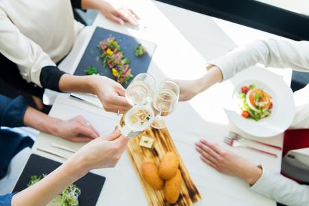 pan y vino: gente, fiestas, celebración y estilo de vida concepto - cerca de la mujer tintinean los vidrios del champán en restaurante
