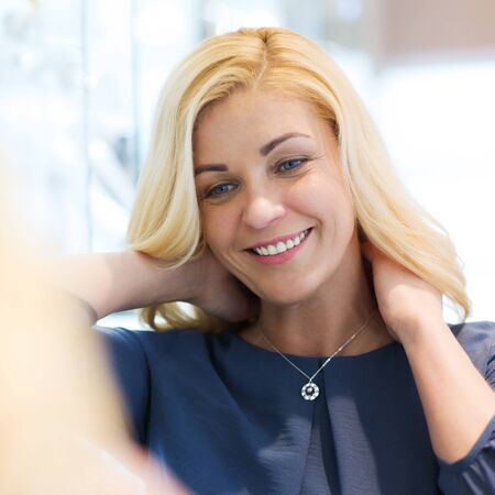 shopper: sale, consumerism, shopping and people concept - happy woman choosing and trying on pendant at jewelry store Stock Photo