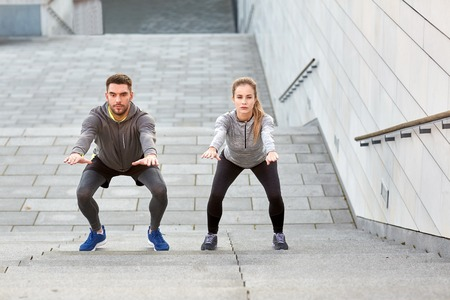 outdoor sport: fitness, sport, exercising and healthy lifestyle concept - man and woman doing squats outdoors