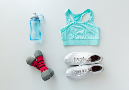 water sports: sport, fitness, healthy lifestyle and objects concept - close up of female sports clothing, dumbbells and bottle set