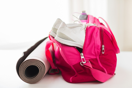 sport, fitness, healthy lifestyle and objects concept - close up of female sports stuff in bag