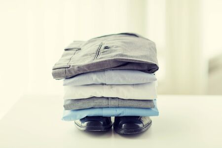 ironed: business, clothes, housekeeping and objects concept - close up of ironed and folded shirts, trousers and formal shoes on table at home