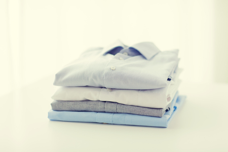 clean clothes: ironing, laundry, clothes, housekeeping and objects concept - close up of ironed and folded shirts on table at home Stock Photo