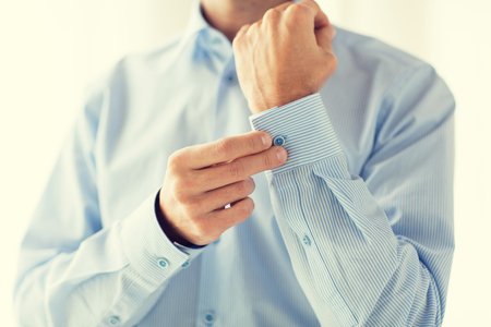 formal dressing: people, business, fashion and clothing concept - close up of man fastening buttons on shirt sleeve at home
