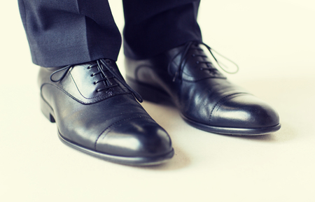 foot gear: people, business, fashion and footwear concept - close up of man legs in elegant shoes with laces or lace boots Stock Photo