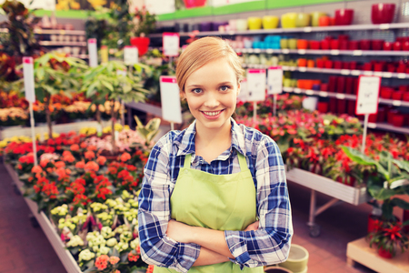 florist shop: people, gardening and profession concept - happy woman with flowers in greenhouse Stock Photo