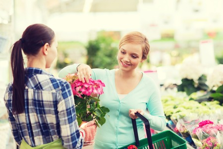 indoor plants: people, gardening, shopping, sale and consumerism concept - happy gardener helping woman with choosing flowers in greenhouse Stock Photo