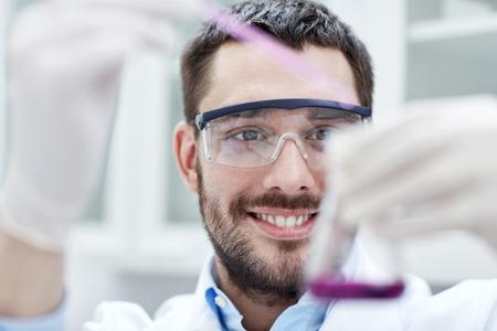 ciencia, química, la tecnología, la biología y la gente concepto - joven científico mezclar reactivos de frascos de vidrio y hacer pruebas o investigación en laboratorio clínico